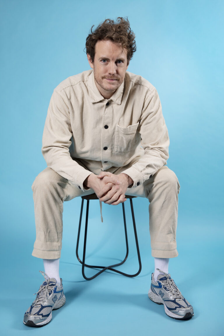 Bart Snijders, founder of Sprints & Sneakers sitting on a chair infront of a bluescreen