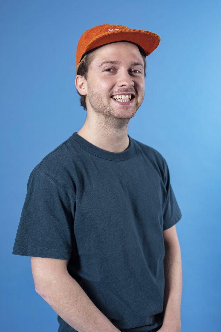 Max, medewerker van Sprints & Sneakers die voor een blauw scherm staat