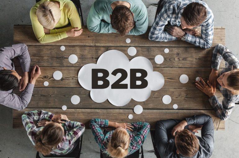 Op de foto zie je acht mensen vergaderen met in het midden daarvan een B2B logo.