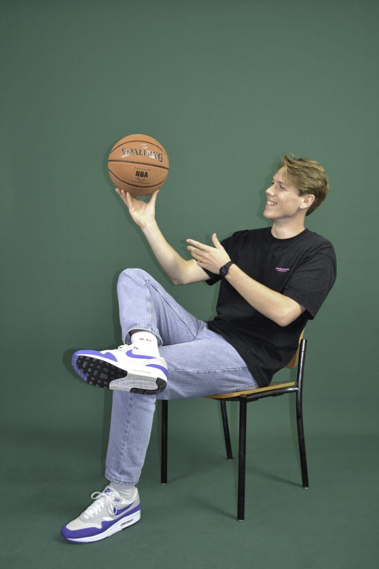 Een jongen met een basketbal in zijn hand.
